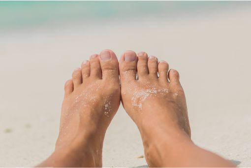 Sandy feet with beach in the background